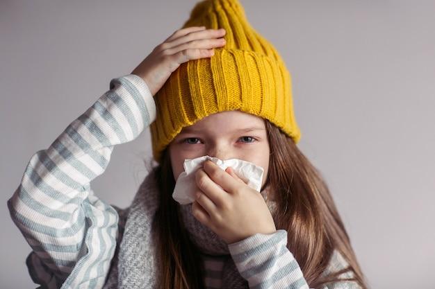 病気の少女がウイルス性疾患を患っており、不健康な子供が鼻をかむ
