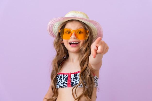 수영복을 입은 조금 놀란 소녀가 손가락을 앞으로 가리킵니다.