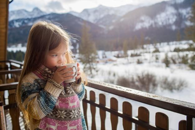 冬の山の背景に甘い女の子がお茶を飲んでいます。