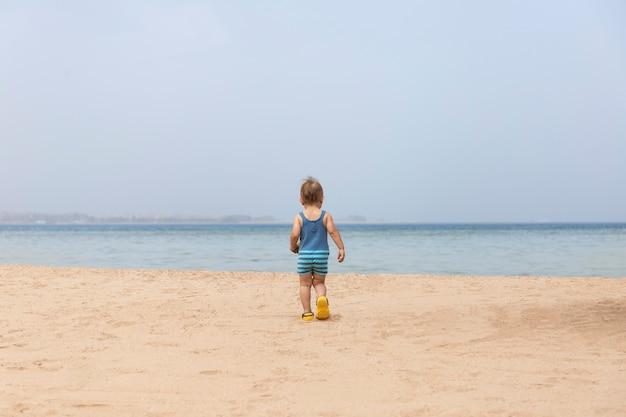 日焼け止めの水着を着た小さな幼児の男の子が泳ぎたいと思って海に向かって走っています。
