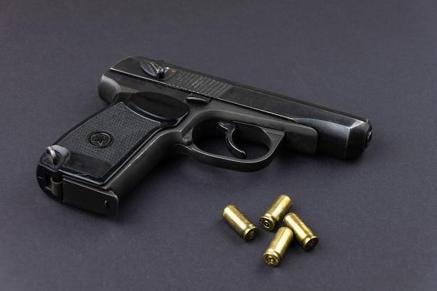 장전 된 권총과 카트리지는 검은 색 표면에 나란히 놓여 있습니다.