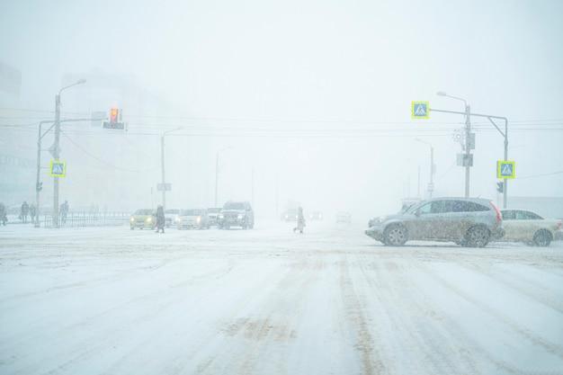 大雪、車、歩行者、道路の間に交通高速道路が満載