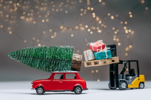 Погрузчик загружает подарки в красную машину с елкой на крыше. на фоне праздничных огней.