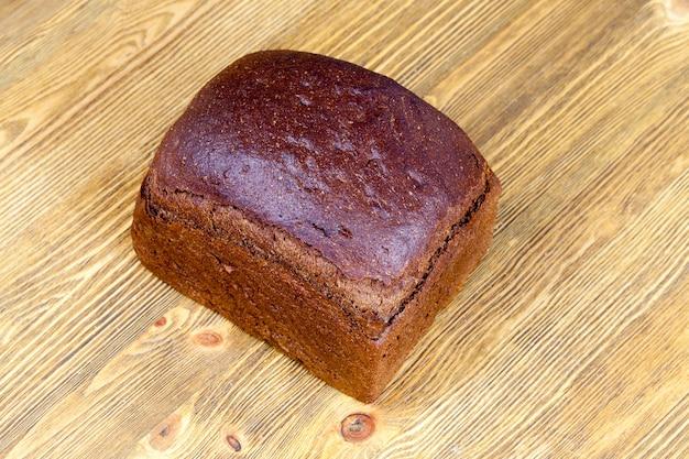 사각형 형태로 구운 검은 색의 신선한 호밀 빵 한 덩어리
