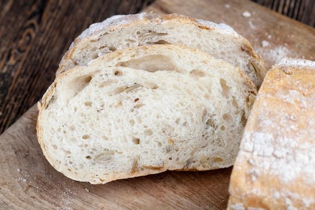 調理中のテーブルの上の焼きたての小麦パン、カボチャの種と亜麻の種が入った柔らかい焼きたてのパン