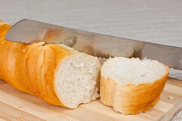 Буханка домашнего хлеба и кусок хлеба на деревянной доске ножом для хлеба.