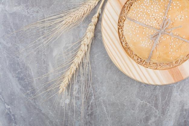 나무 보드에 귀리 곡물과 흰 빵 한 덩어리