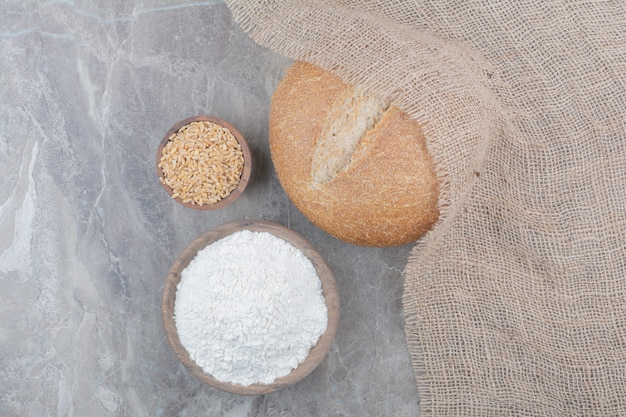 大理石の表面にオーツ麦の穀物と小麦粉が入った白パン一斤