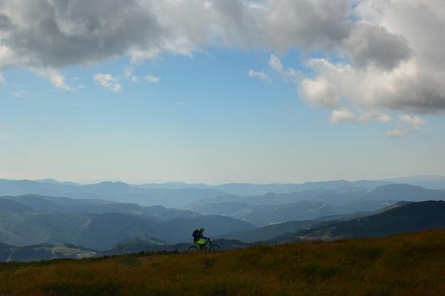 Одинокий велосипедист едет на вершине горы летом и на фоне далеких гор