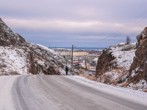 北極の丘の間の曲がりくねった道を歩いている男の一人の姿。チェベルカ。