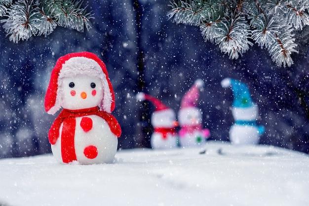Одинокий снеговик на расстоянии от других снеговиков в лесу во время снегопада