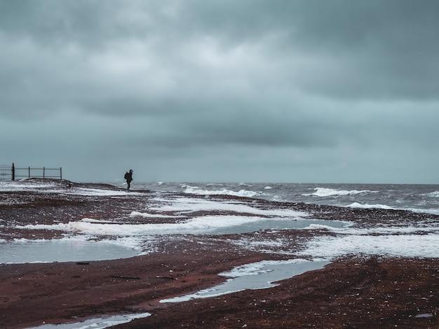 強風と空飛ぶ泡の雲のある荒れ狂う嵐の海岸で一人の旅行者。嵐の中の白海。コラ半島。