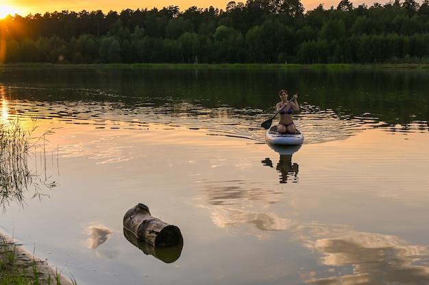 Одинокая женщина катается на sup board по озеру, окруженному травой и густым зеленым лесом на закате. озеро лебяжье, казань.