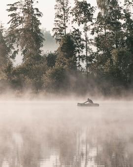 Одинокий рыбак в лодке на реке туманным утром. вертикальная ориентация.