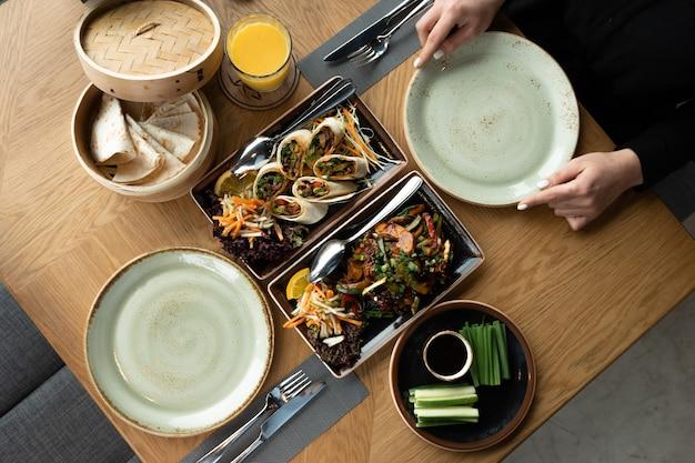 Одинокая девушка за накрытым столом в ресторане ждет покойного парня или девушку. утка по-пекински и острые блюда. ужин в ресторане.