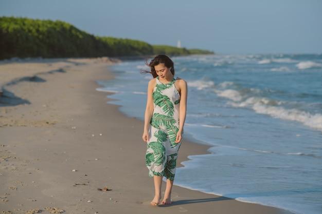孤独な少女が濡れた砂の上を歩いています。ビーチの上を歩く美しいアジアの女性。