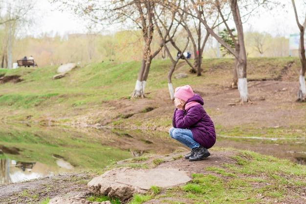 외로운 소녀가 앉아서 공원의 호수에 손으로 얼굴을 가리고 울고 있습니다. 정신 건강
