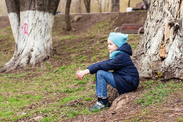 외로운 소녀가 공원에있는 나무 뿌리에 고독하게 앉아 멀리서 바라본다. 정신 건강