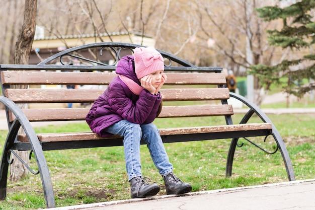 외로운 소녀는 슬픈 얼굴로 공원 벤치에 앉아있다. 정신 건강. 십대 시절