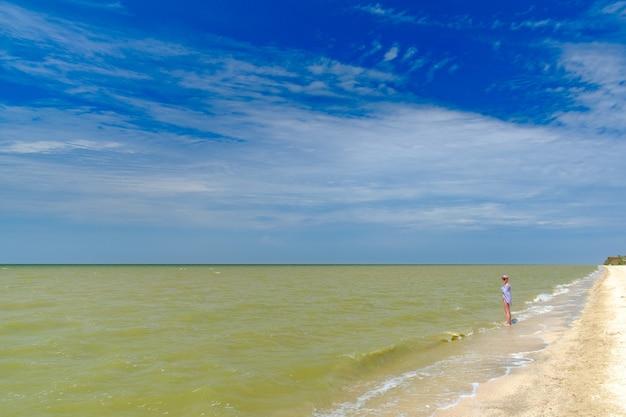 외로운 소녀가 수건에 싸인 서핑 라인의 물 위에 서 있습니다. 해변 리조트에서 여름 화창한 날.