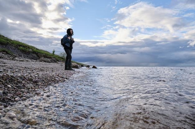 외로운 소녀가 해안을 따라 여행합니다. 도시 밖에서의 활동적인 휴식. 야생 동물. 나쁜 날씨.