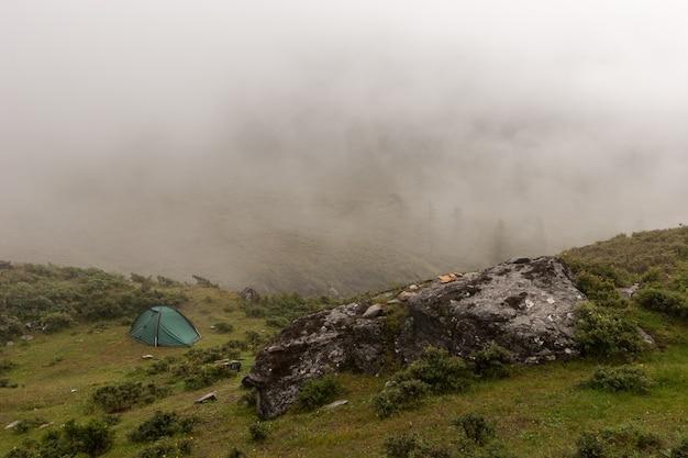 Одинокая зеленая палатка стоит в тумане в горах. большой валун на переднем плане. вокруг зеленая растительность. скопируйте пространство. по горизонтали.