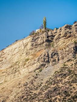 崖の上の孤独な家。グニブの本物のダゲスタン山の村。ロシア。垂直方向のビュー。