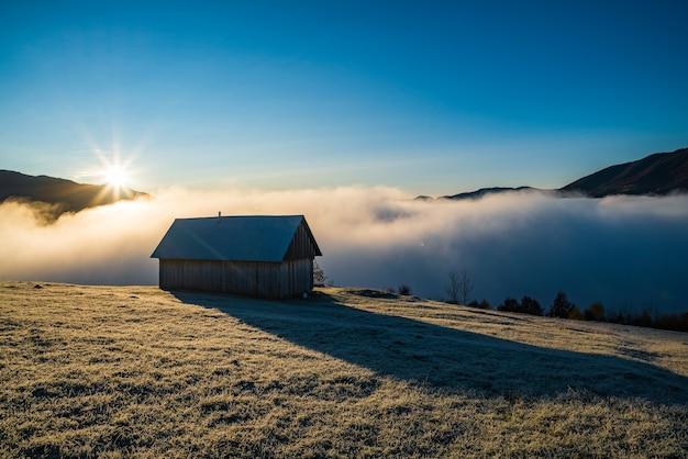 孤独な家が美しい空と白い霧を背景にクリアリングに立っています