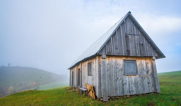 Одинокий серый домик стоит на свежем влажном зеленом лугу среди густого серого тумана.