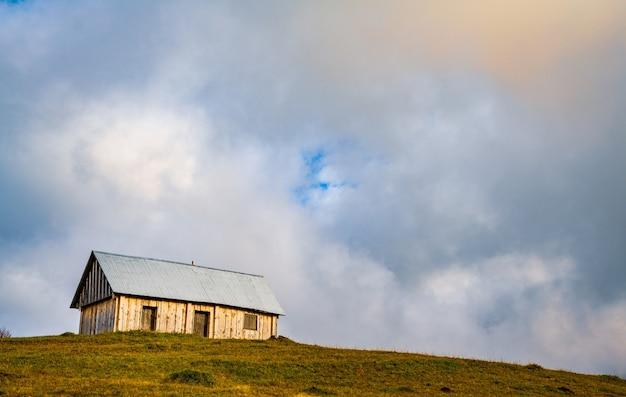 孤独な小さな灰色の家は、濃い灰色の霧の中で新鮮な湿った緑の牧草地に立っています