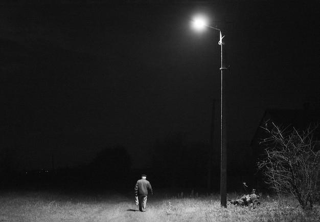 외로운 남자가 밤에 등불 아래에 간다