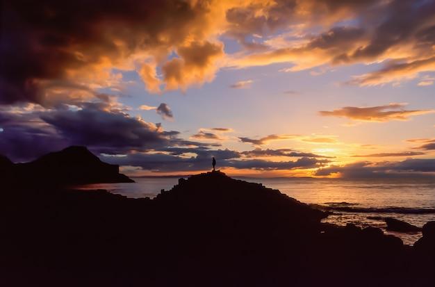 Одинокий мужчина, стоящий на скалах, наблюдает за красивым закатным светом на берегу океана