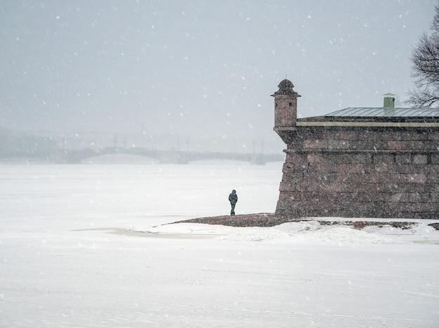 後ろを歩いている孤独な男。降雪のある美しい春の街並み。