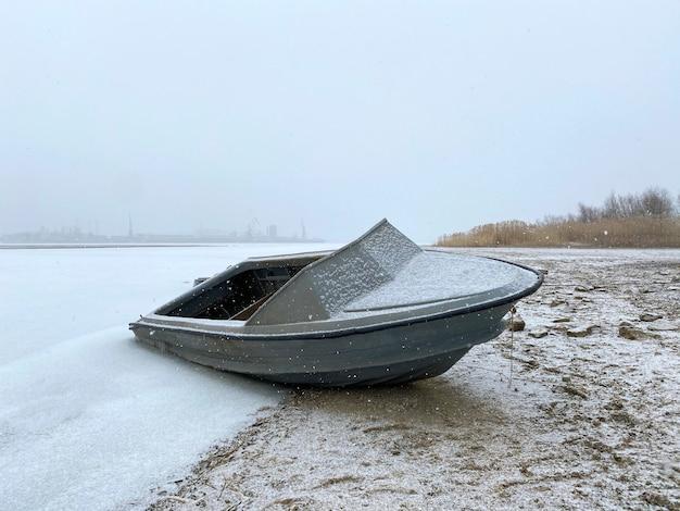 Одинокая моторная рыбацкая лодка припаркована под снегом на зимней стоянке на берегу реки.