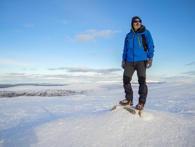 외로운 산악인이 태양 위로 구름 위의 눈 덮인 산에서 휴식을 취하십시오.