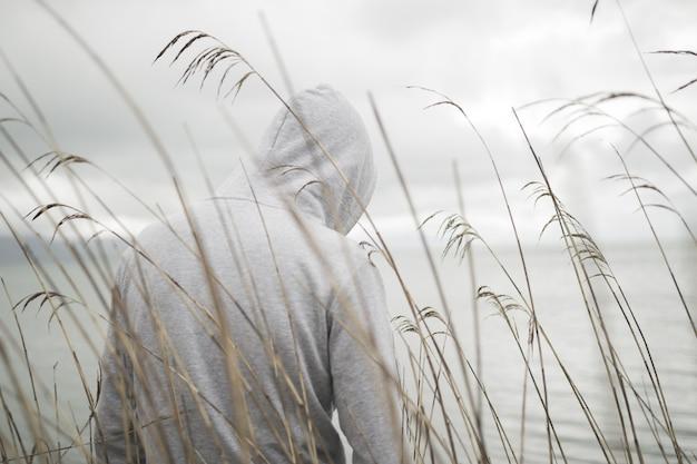 Одинокий грустный человек сзади в толстовке с капюшоном сидит у моря и думает о жизни
