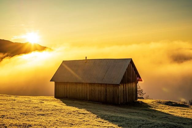 美しい青い空、明るい太陽、白い霧を背景に、凍った牧草地に孤独な小さな家が立っています。