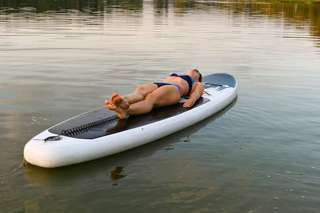 孤独な女性が日没時に湖に囲まれたsupbordに横たわっています。カザンのlebyazhye湖。夏の風景。アクティブな週末の休暇は、屋外の野生の自然です。