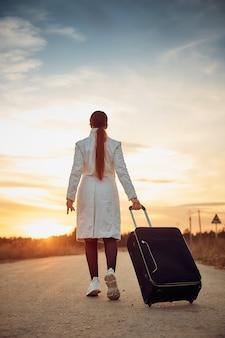 スーツケースを持った孤独な女性が、旅行のコンセプトである空の道を歩いている