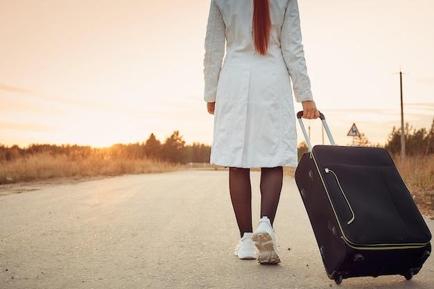 スーツケースを持った孤独な女性が空の道を歩いている