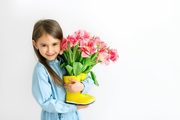 Длинноволосая девушка держит желтые резиновые сапоги с букетом тюльпанов в подарок маме.