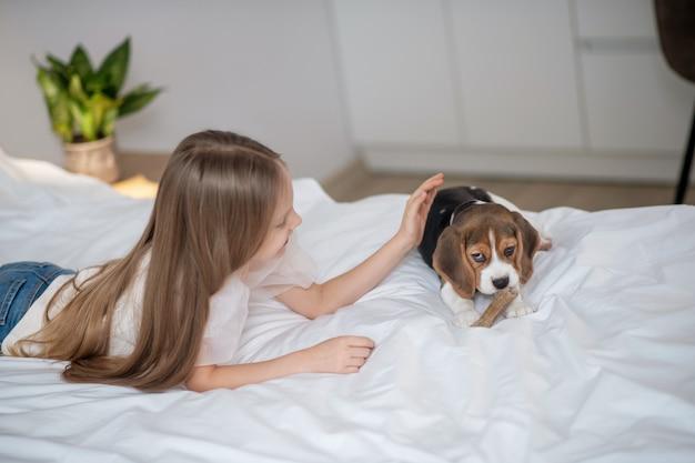 Длинноволосая девочка играет со своим щенком на кровати