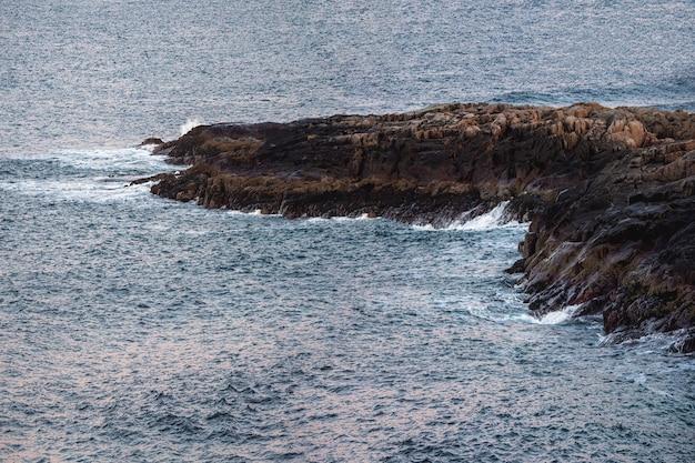 海に突き出た長い岩の崖。バレンツ海の素晴らしいパノラマの山の風景。チェベルカ。 Premium写真
