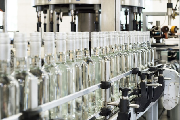 コンベア上のガラス瓶の長い列。アルコール飲料の製造。