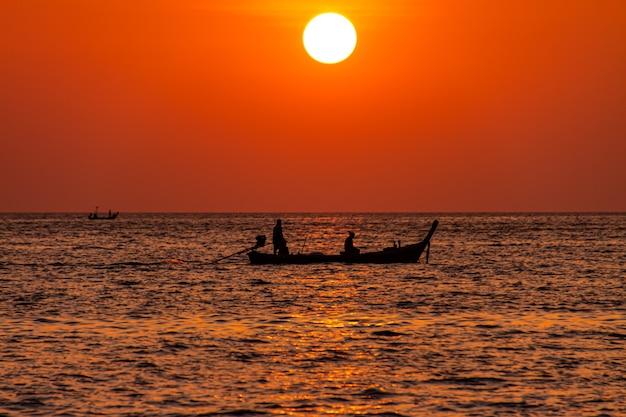 プーケットのパトンビーチで夕日を眺める人間のシルエットのロングテールボート。