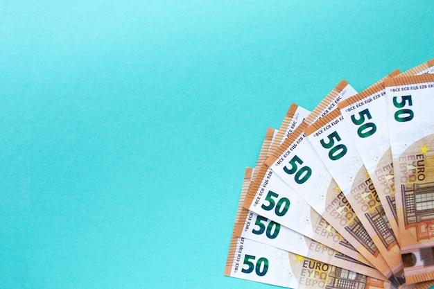 Много 50 евро банкноты выложены на синем фоне. лежите веером в правом нижнем углу. понятие денег и финансов. с местом для текста.