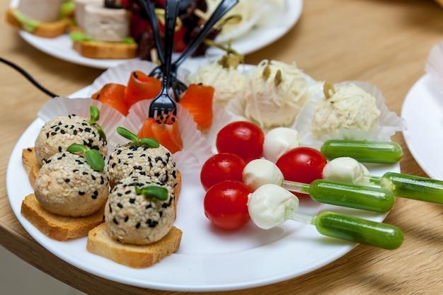 木製のテーブルの白いプレートにチーズと野菜の前菜がたくさん。