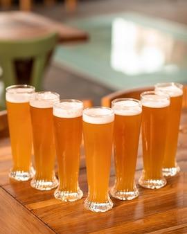 たくさんのビールを飲むグラス、テーブルの上のマグカップ
