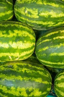 Много больших сладких зеленых органических арбузов на турецком рынке фермеров в анталии, турция. питание и витамины. здоровая сырая диетическая пища