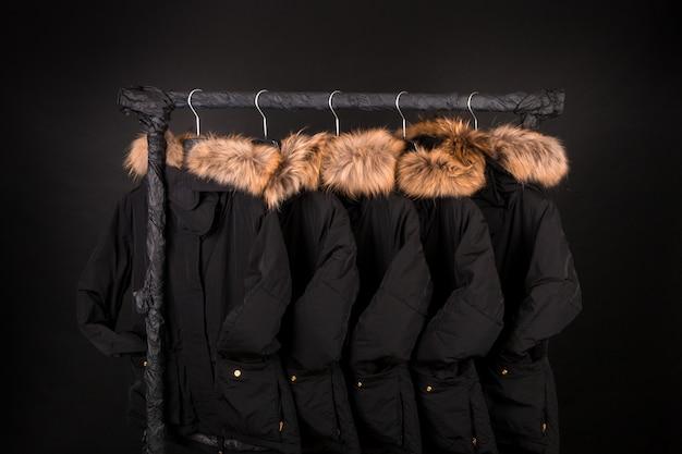 많은 검은 코트, 후드에 모피가 달린 재킷이 옷걸이에 걸려 있습니다. 검정색 배경.